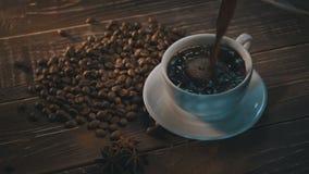 Tazza di caffè nero con i fagioli sopra la tavola di legno di lerciume video d archivio