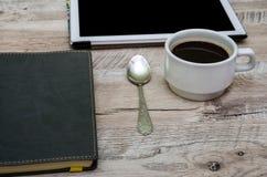 Tazza di caffè nero, della compressa e del blocco note su un fondo di legno fotografia stock libera da diritti