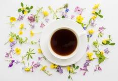 Tazza di caffè nero sui precedenti di piccoli fiori e foglie Fotografia Stock