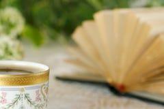 Tazza di caffè o tè bianca nel giardino con un libro aperto Immagini Stock Libere da Diritti