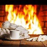 Tazza di caffè o tè bianco, sciarpa di lana, guanti e cappuccio sulla tavola di legno vicino al camino Fotografia Stock Libera da Diritti