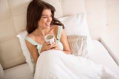 Tazza di caffè piacevole della tenuta della ragazza a letto Immagini Stock Libere da Diritti