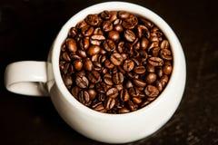 Tazza di caffè in pieno dei chicchi di caffè Primo piano Fotografia Stock