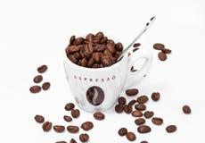 Tazza di caffè in pieno dei fagioli e del cucchiaio Immagini Stock Libere da Diritti