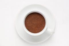 Tazza di caffè in pieno di caffè macinato su soucer contro fondo bianco, vista superiore Immagini Stock Libere da Diritti