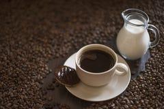 Tazza di caffè in pieno di caffè sul piatto con i biscotti ed i chicchi di caffè arrostiti sulla tavola di legno Immagini Stock