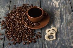 Tazza di caffè di recente preparato sui chicchi di caffè sparsi, accanto ai cuori della corda, su una vecchia tavola Immagini Stock