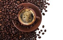Tazza di caffè di recente preparato sul mucchio dei chicchi di caffè isolati su bianco Immagine Stock