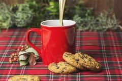 Tazza di caffè rossa, biscotti della vaniglia con di pepita di cioccolato Immagini Stock