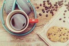 Tazza di caffè rossa, cuffia d'annata e biscotti di pepita di cioccolato Fotografia Stock Libera da Diritti