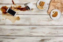 Tazza di caffè rovesciata sulla tavola di legno immagini stock libere da diritti