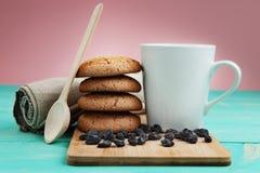 Tazza di caffè saporito con i dadi ed i biscotti sopra la tavola di legno d'annata Fotografia Stock