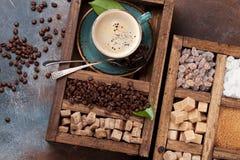 Tazza di caffè, semi di cacao torrefatti e zucchero bruno immagini stock