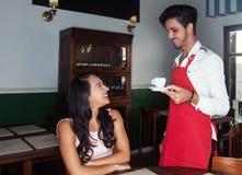 Tazza di caffè servente del cameriere ispano ad un ospite Fotografia Stock