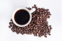Tazza di caffè sistemata con i chicchi di caffè arrostiti freschi Fotografie Stock