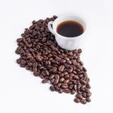 Tazza di caffè sistemata con i chicchi di caffè arrostiti freschi Fotografia Stock