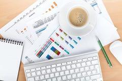 Tazza di caffè sopra le carte con i numeri ed i grafici Immagine Stock