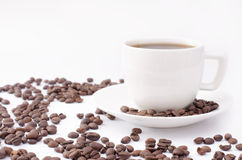 Tazza di caffè su un fondo bianco con i fagioli Fotografia Stock