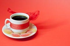 Tazza di caffè su una priorità bassa rossa Immagine Stock