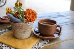 Tazza di caffè su una tavola con un fiore sulla via Immagini Stock
