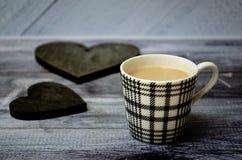 Tazza di caffè su una tavola di legno con due cuori d'annata di legno scuri immagine stock