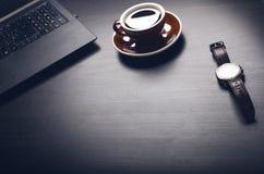 tazza di caffè su una tavola scura Concetto dell'affare Computer portatile, caffè, orologio fotografia stock libera da diritti