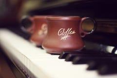 Tazza di caffè su una vecchia tastiera di piano mentre componendo Tempo di sera ed alcuni raggi del sole Tazza da caffè sulla tas Fotografie Stock