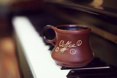 Tazza di caffè su una vecchia tastiera di piano mentre componendo Tempo di sera ed alcuni raggi del sole Tazza da caffè sulla tas Fotografia Stock