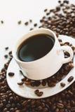 Tazza di caffè sui fagioli. Fotografia Stock