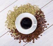 Tazza di caffè sui fagioli Fotografia Stock