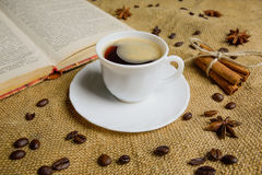 Tazza di caffè sui precedenti di tela da imballaggio con un libro Chicchi di caffè Anice immagini stock libere da diritti