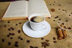 Tazza di caffè sui precedenti di tela da imballaggio con un libro Chicchi di caffè Anice Fotografia Stock