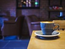 Tazza di caffè sui sedili interni del caffè del ristorante della tavola fotografia stock