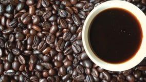 Tazza di caffè sul mucchio dei chicchi di caffè archivi video