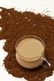 Tazza di caffè sulla priorità bassa della polvere del caffè solubile Fotografia Stock