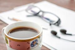 Tazza di caffè sulla tavola di legno con i vetri, cuffie Fotografia Stock