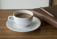 Tazza di caffè sulla tavola di legno con il libro del diario Fotografie Stock Libere da Diritti
