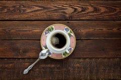 Tazza di caffè sulla tavola di legno scura con il piatto ed il cucchiaio Vista superiore Immagini Stock Libere da Diritti