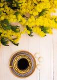 Tazza di caffè sulla tavola e sulla mimosa di legno Fotografie Stock