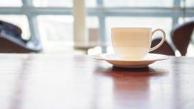 Tazza di caffè sulla tavola nell'interno del negozio del caffè Immagine Stock