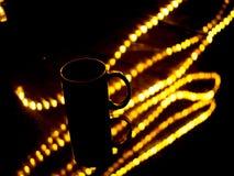 Tazza di caffè sulla tavola nera con illuminazione nel fondo immagine stock