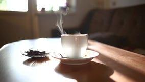 Tazza di caffè sulla tavola in salone Vapore caldo dalla tazza di caffè su una finestra leggera video d archivio