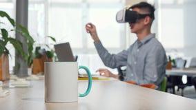 Tazza di caffè sulla tavola, uomo facendo uso dei vetri del vr 3d sul lavoro sui precedenti stock footage