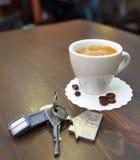 Tazza di caffè sullo scrittorio e sulle chiavi Immagine Stock