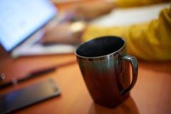 Tazza di caffè sullo studente di college Studying At Night dello scrittorio Immagini Stock Libere da Diritti