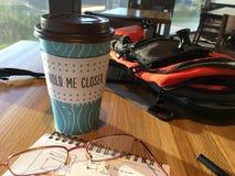 Tazza di caffè in un caffè con & in un x22; tengami closer& x22; messaggio immagine stock