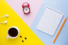 Tazza di caffè, una sveglia e un taccuino con una matita sugli ambiti di provenienza variopinti Il concetto dell'affare Fotografie Stock Libere da Diritti