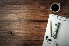 Tazza di caffè, vetri, penna, cuffie e nota sulla tavola di legno scura Immagini Stock