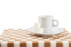 Tazza di caffè vuota su un piattino con tre cubi di zucchero su uno stan Fotografie Stock