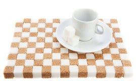 Tazza di caffè vuota su un piattino con tre cubi di zucchero su uno stan Immagine Stock